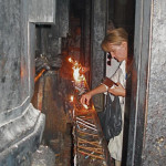 Lighting candles on girder that braced the Tomb of Christ before restoration in 2017 (Seetheholyland.net)